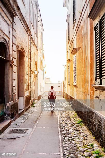 Rear view of man walking on road amidst buildings