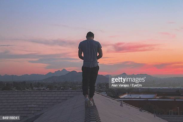 Rear View Of Man Walking On Rooftop Against Sky During Sunset