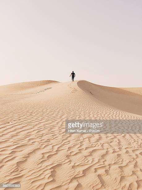 rear view of man walking on sand dune against clear sky - sand dune stock pictures, royalty-free photos & images