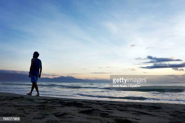 Rear View Of Man Walking On Shore At Beach Against Sky During Sunset