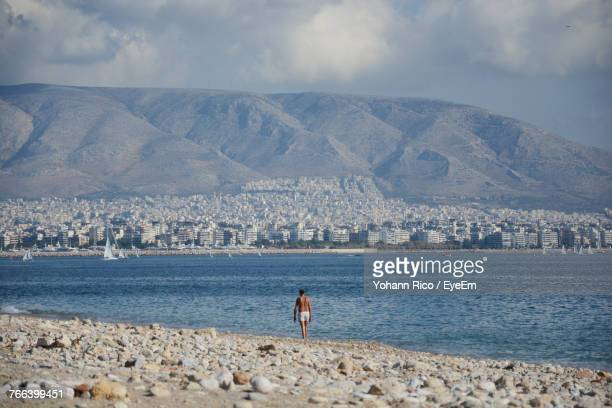 rear view of man walking on shore at beach - piraeus stock photos and pictures