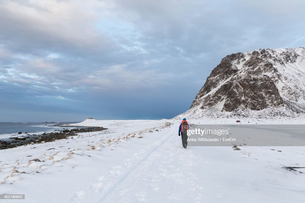 Rear View Of Man Walking On Snow Covered Beach Against Cloudy Sky Stock Photo