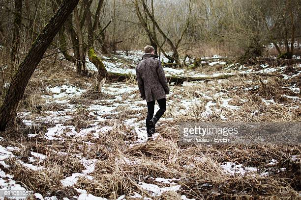 Rear View Of Man Walking On Snow Covered Field In Forest