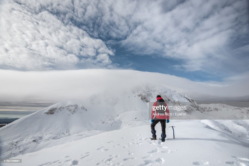 Rear View Of Man Walking On Snowcapped Mountain Against Sky : Foto stock