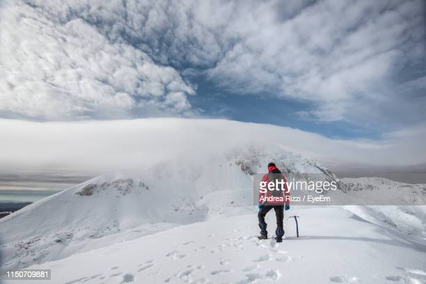 rear view of man walking on snowcapped mountain against sky - andrea rizzi foto e immagini stock