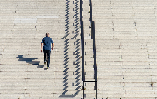 Rear View Of Man Walking On Staircase During Sunny Day - gettyimageskorea