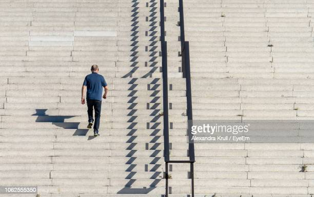 Rear View Of Man Walking On Staircase During Sunny Day