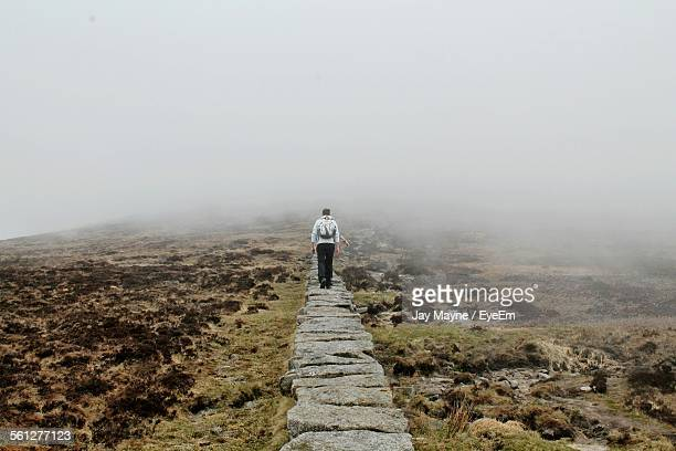 Rear View Of Man Walking On Stone Walk