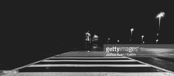 Rear View Of Man Walking On Street Against Sky At Night