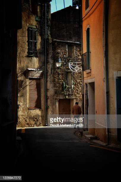 rear view of man walking on street amidst buildings in city - guy carcassonne photos et images de collection