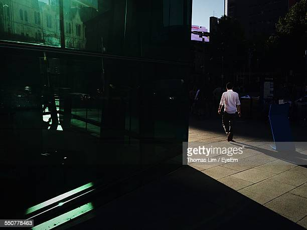 Rear View Of Man Walking On Street At Federation Square