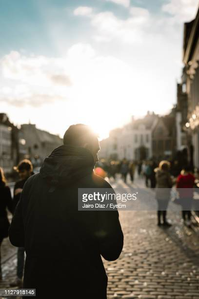 rear view of man walking on street in city against sky - flanders belgium stock pictures, royalty-free photos & images