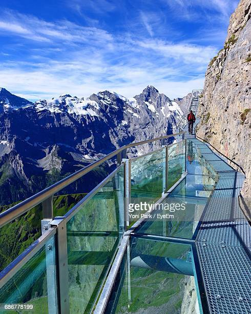 Rear View Of Man Walking On Walkway Against Mountains At Schilthorn