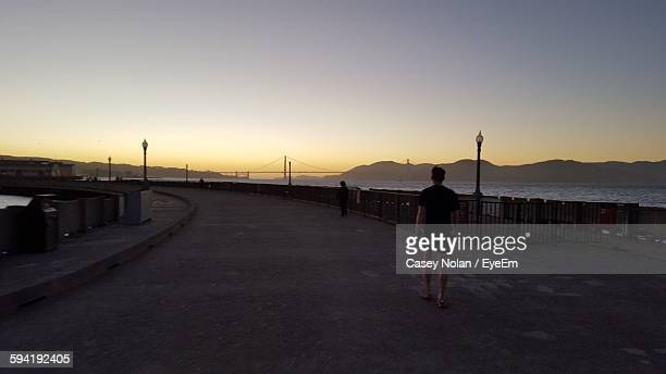 rear view of man walking on walkway with golden gate bridge against sunset sky - casey nolan stock pictures, royalty-free photos & images