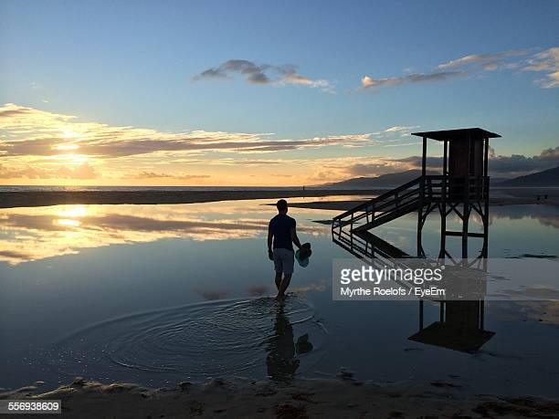 Rear View Of Man Walking On Water With Reflection On Beach During Sunset