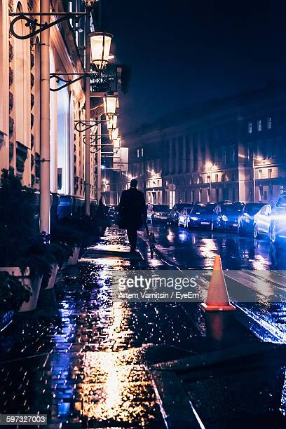 Rear View Of Man Walking On Wet Footpath In City At Night