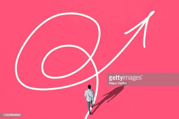 rear view of man walking on white tangled arrow - guidance stock pictures, royalty-free photos & images