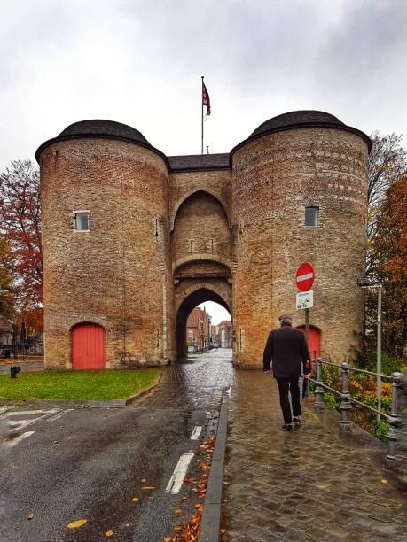 Rear View Of Man Walking Towards Historic Gate Building Against Sky