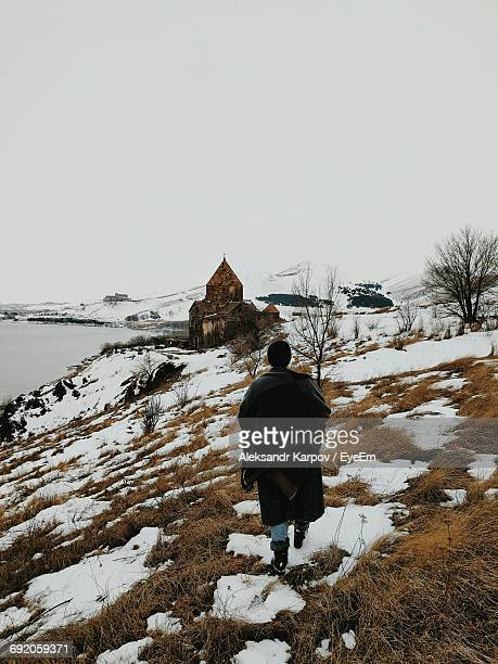 Rear View Of Man Walking Towards Old Church On Snow Covered Hill By Lake Against Clear Sky