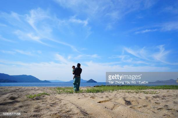 Rear View Of Man Walking With Baby On Sand At Beach Against Sky