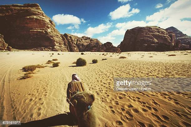 Rear View Of Man Walking With Camel In Wadi Rum