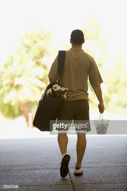 Rear view of man walking with golf clubs and golf balls
