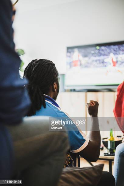 rear view of man watching soccer match with friend at home - friendly match stockfoto's en -beelden