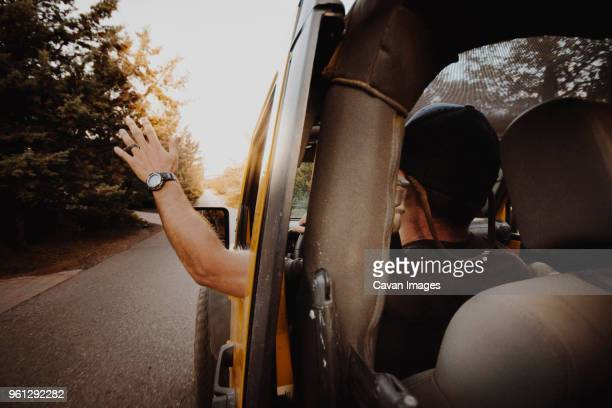 rear view of man waving through off-road vehicle window while driving on road - jeep stock pictures, royalty-free photos & images