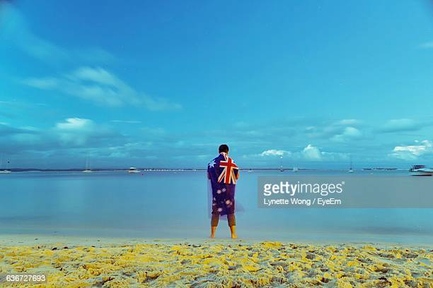 rear view of man wearing australian flag standing at shoal bay - australian flag stock pictures, royalty-free photos & images