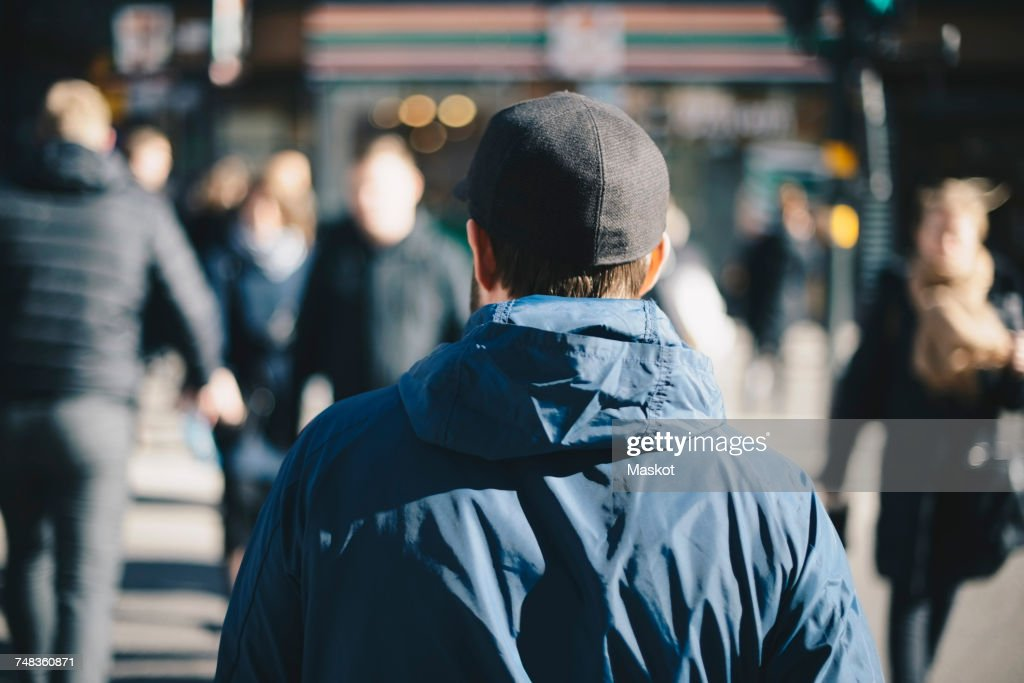 Rear view of man wearing blue jacket on city street during winter : Stock Photo