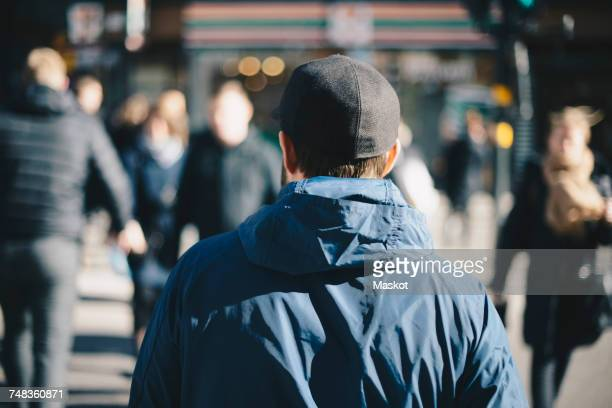 Rear view of man wearing blue jacket on city street during winter