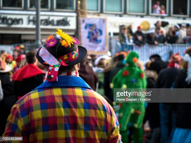 rear view of man wearing colorful shirt while standing in city - karneval stock-fotos und bilder