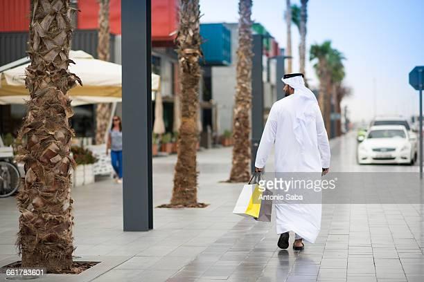 Rear view of man wearing dishdasha walking along street carrying shopping bags, Dubai, United Arab Emirates