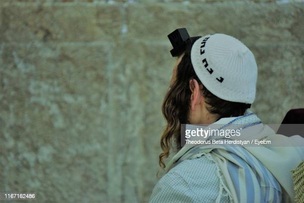 rear view of man wearing hat and tefillin against wall - judaism stock pictures, royalty-free photos & images