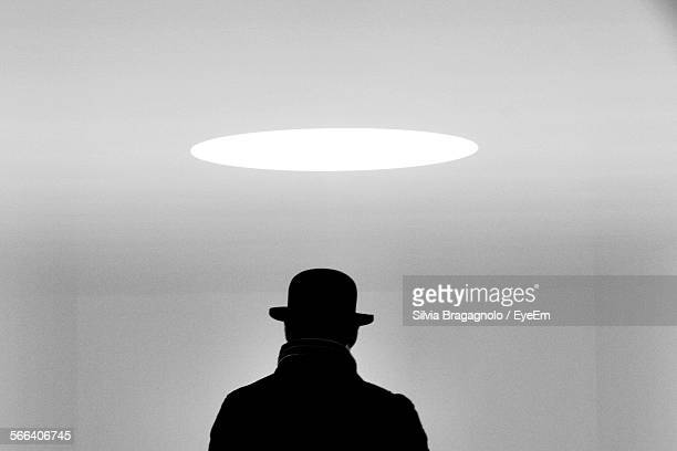rear view of man wearing hat standing in illuminated room - detective stock pictures, royalty-free photos & images