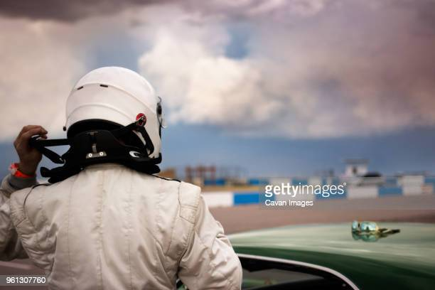 rear view of man wearing helmet standing by car against cloudy sky - motor show stock pictures, royalty-free photos & images