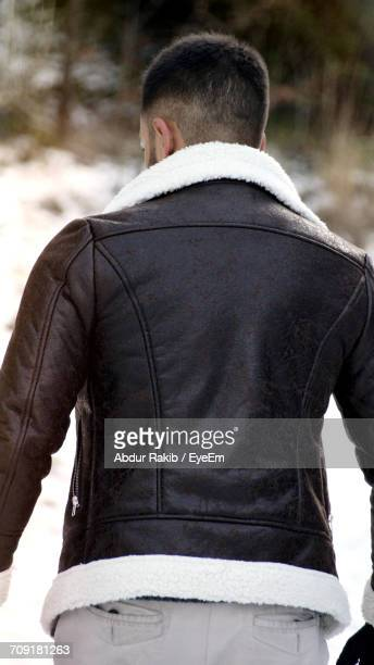 Rear View Of Man Wearing Leather Jacket Standing On Field During Winter
