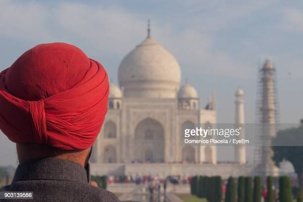 rear view of man wearing red turban against taj mahal - sikh stock pictures, royalty-free photos & images