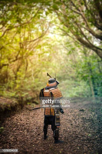 rear view of man wearing samurai costume amidst trees in forest - samurai stock pictures, royalty-free photos & images