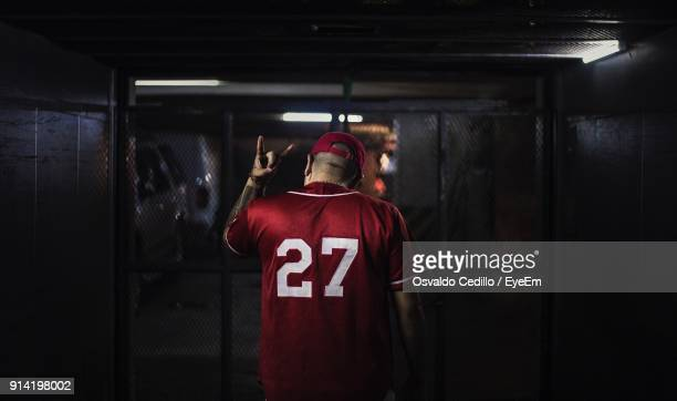 rear view of man wearing sports uniform in darkroom - locker room stock pictures, royalty-free photos & images