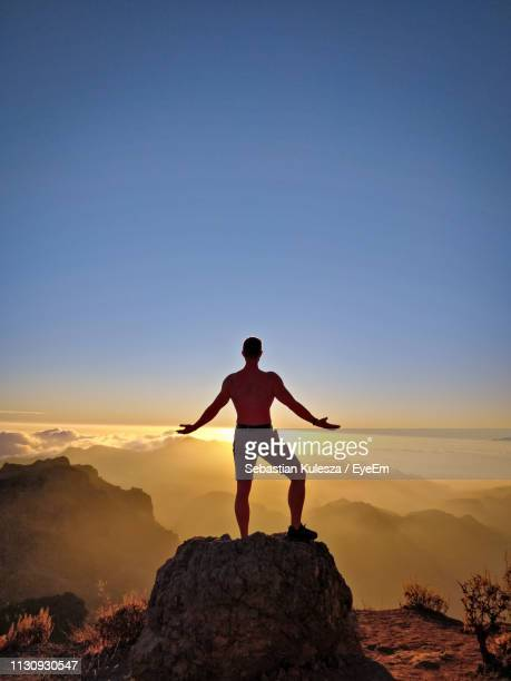 rear view of man wit arms outstretched standing on rock during sunset - tejeda stock pictures, royalty-free photos & images