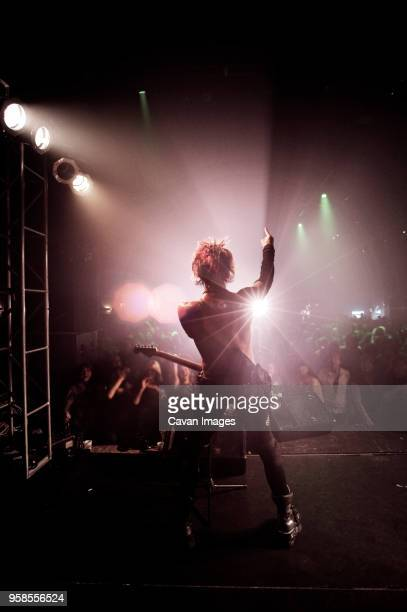 rear view of man with arm raised performing at music concert - rock musician stock pictures, royalty-free photos & images