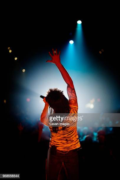 Rear view of man with arm raised singing at concert