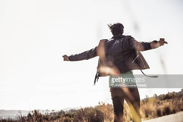 Rear view of man with arms open, wearing leather jacket, Franchoek, South Africa