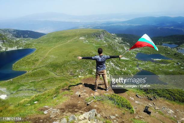 rear view of man with arms outstretched holding flag while standing on mountain - krasimir georgiev stock photos and pictures