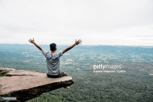 rear view of man with arms outstretched sitting on mountain - arms outstretched stock pictures, royalty-free photos & images