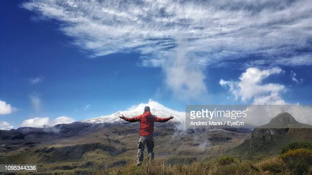rear view of man with arms outstretched standing on landscape against sky - nevado del ruiz stock photos and pictures