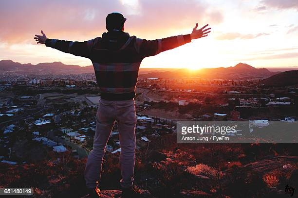 rear view of man with arms outstretched standing on rock against cityscape against sky during sunset - テキサス州エルパソ市 ストックフォトと画像