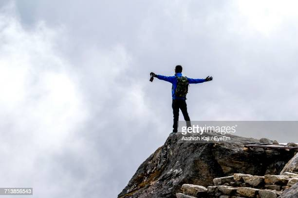 Rear View Of Man With Arms Outstretched Standing On Rock Against Cloudy Sky