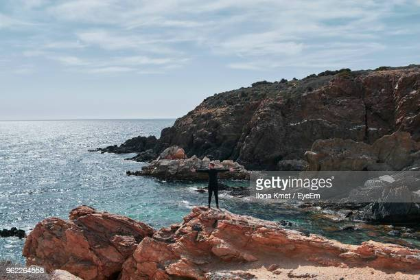 Rear View Of Man With Arms Outstretched Standing On Rock By Sea